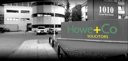 Outside of Howe + Co offices, in grey with the focus on the Howe + Co sign with address picked out in green and yellow lettering.